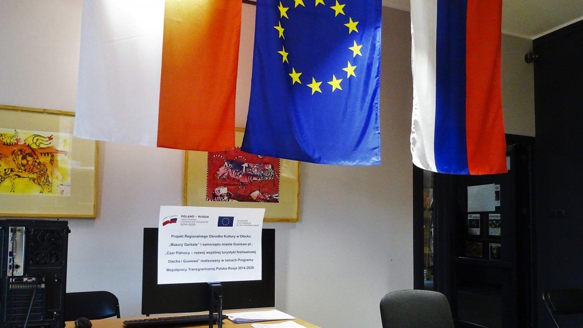 """Na zdjęciu widać trzy flagi: Polski. Unii Europejskiej i Rosji oraz plakat informujący o projekcie """"Czar Północy"""""""